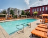 View of the Pool Area at Alpha Mill Apartments, Showing Loungers, Cabanas, and Apartment Buildings in Background